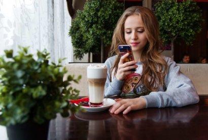 Image_Junge Dame prüft ihr Smartphone in einem Cafehaus