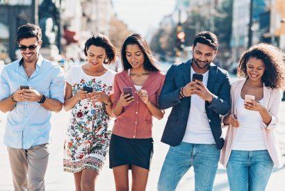 Multiethnische Gruppe junger Menschen, die im Freien in der Stadt SMS schreiben