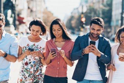 Image_Multiethnische Gruppe junger Menschen, die im Freien in der Stadt SMS schreiben