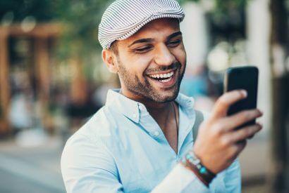 Lächelnder junger Mann prüft Nachrichten auf seinem Handy.