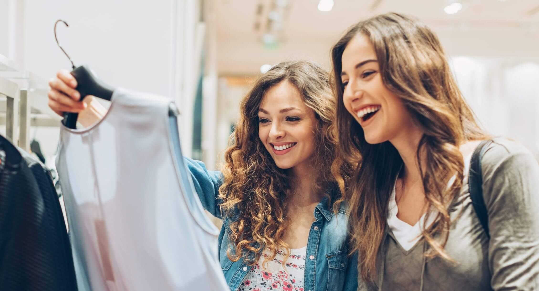 Image_Zwei fröhliche Mädchen beim Einkaufen von Kleidung