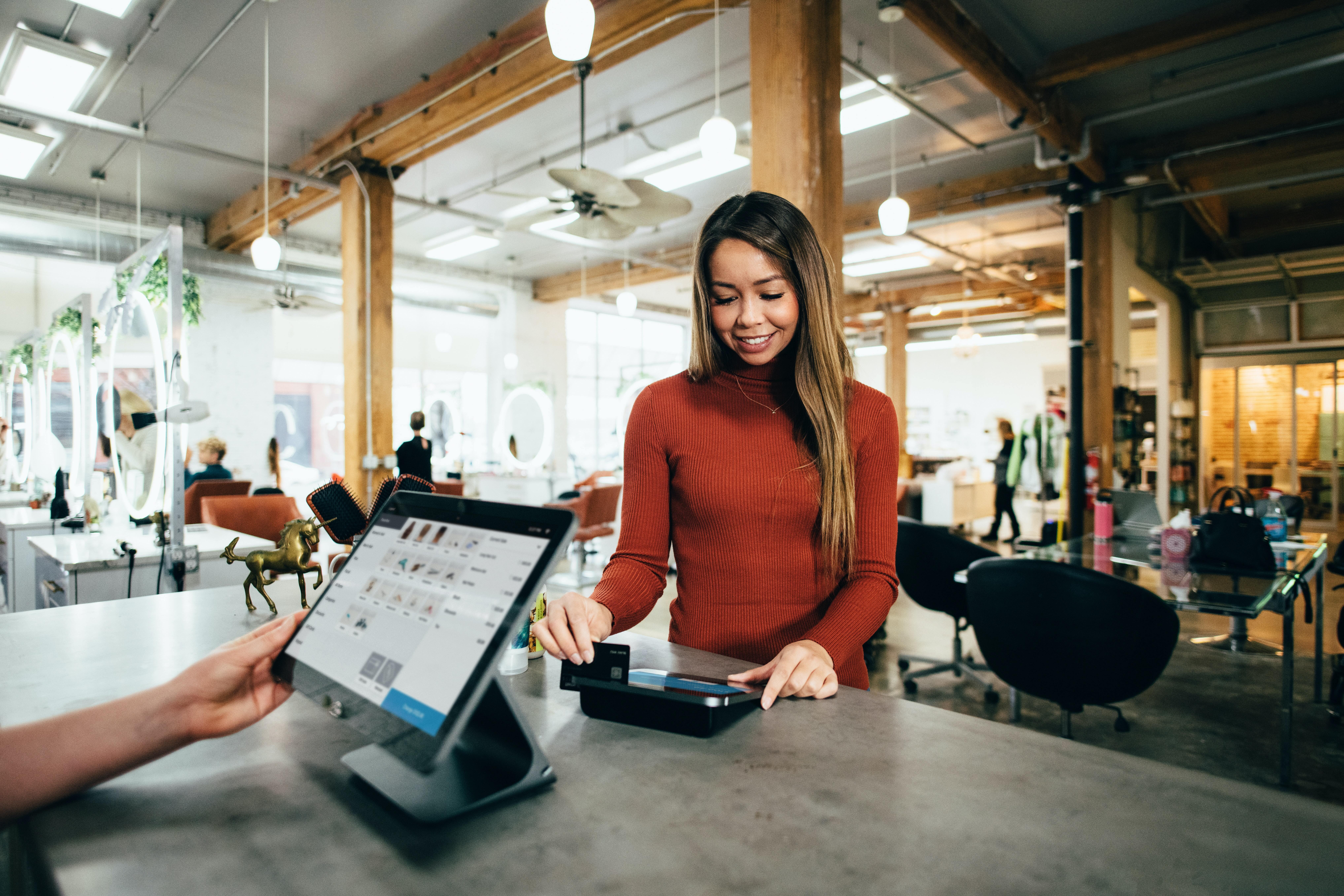 Frau zahlt am POS mit Kreditkarte