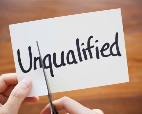 "A paper says ""unqualified"" on it. A person cuts between the word to remove ""un"" from ""qualified."""