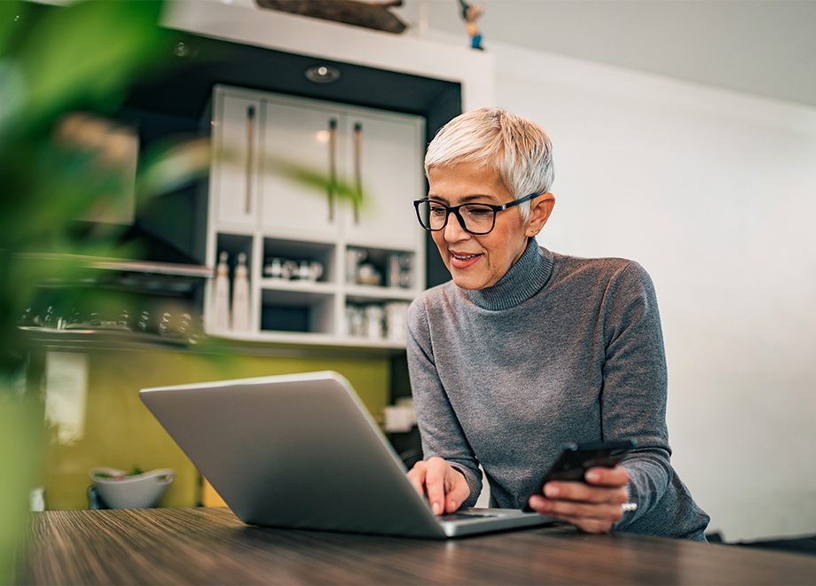 senior woman uses her computer to research senior living