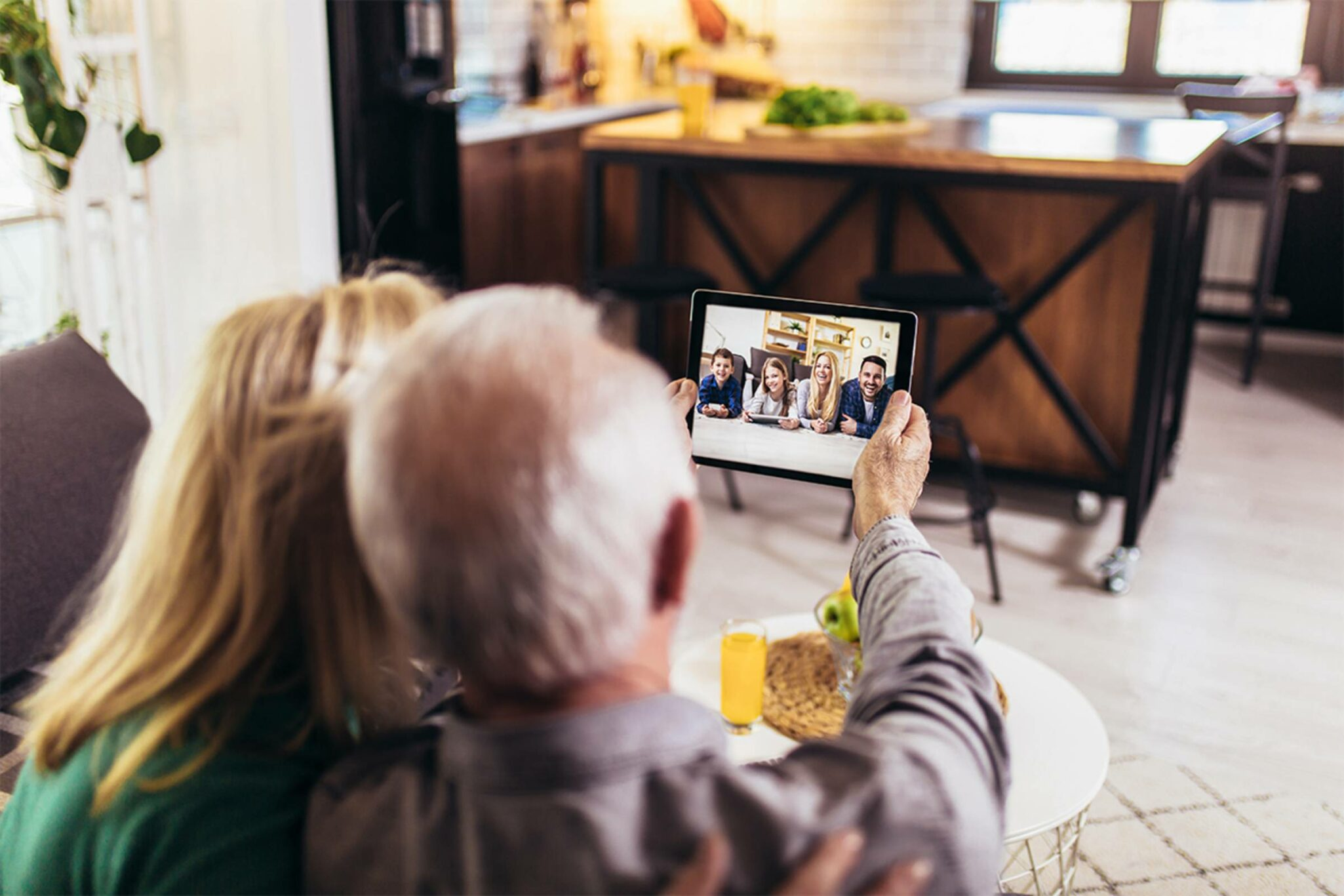 two grandparents facetime their grandkids with ipad