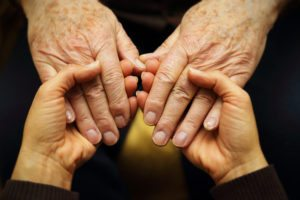 A close up photo of two seniors holding hands