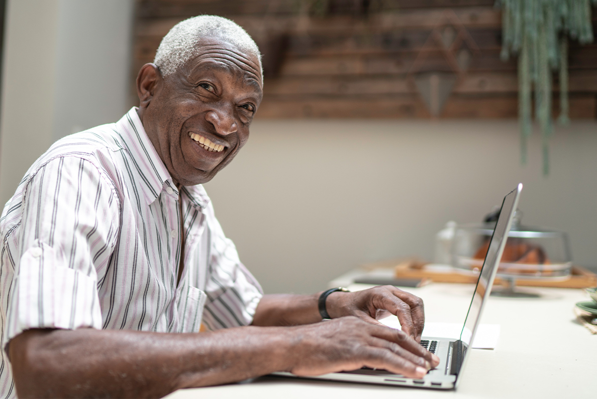 retired senior man smiles as he works in his computer