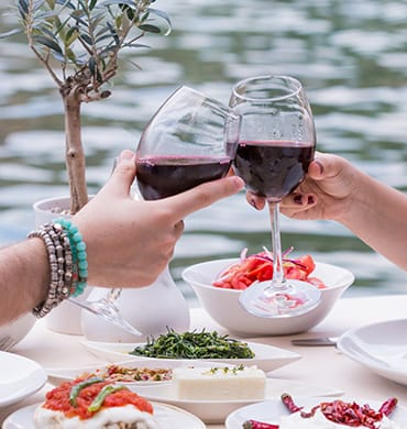 Nippend aan een glas rondborstige rode wijn. Proost! Op Hillside Beach Club!