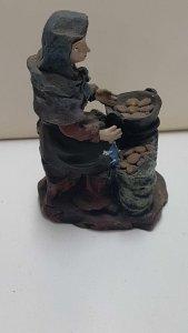 Figura de resina: Mujer sentada cocinando con un fogon de leña. 11 cm de alto