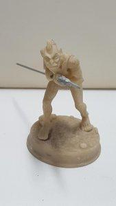 Figura: Humanoide de orejas puntiagudas y pelo largo con una lanza en sus manos