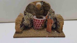 Figura de corcho: Mujer con jarra sobre la cabeza y un pozo al fondo, sobre p...