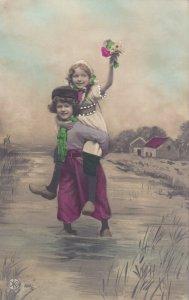 RP: Dutch Children, Girl piggyback on boy crossing creek, 1900-10s