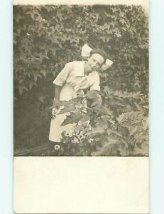 Pre-1918 rppc WOMAN WITH BOW IN HAIR BENDING OVER BY PLANTS r5836