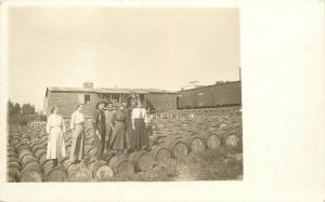 RPPC Postcard Men and Women Stand on Barrels Marked D1800 next to Train cars