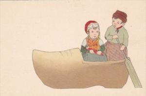 Humour Dutch Children With Paddle Sitting In Wooden Shoe