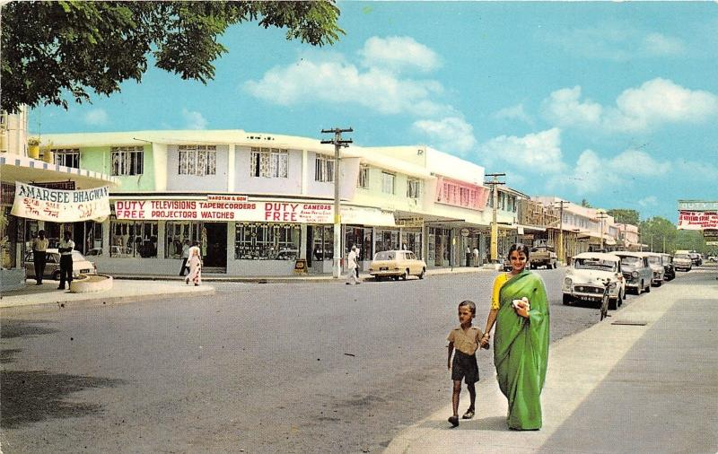 Nadi Fiji~Street Scene~Storefronts~60s Cars~Lady posing w Little Boy~Postcard