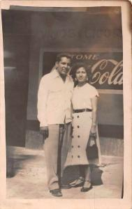Unknown location man and woman in front of Coca Cola sign real photo pc Z18701