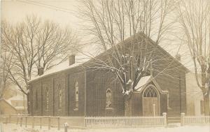 Picket Fence Around a Brick Church~Snow in Yard~Real Photo Postcard c1910 SHARP