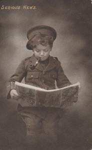 ENGLAND, UK, 00-10s; Young boy dressed as a soldier, reading Paper Serious News