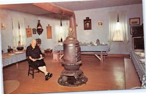 Colony Kitchen, Middle Amana, Iowa - Older Woman reading in front of stove