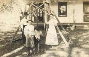 Family Standing Next To Big Wood-Frame Swing Set~Real Photo Postcard c1910