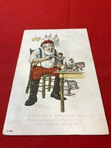 embossed postcard SANTA Making Toys With Robe Off and Sleeves Rolled Up