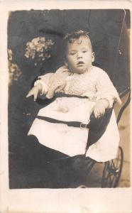 YOUNG CHILD STRAPPED IN CARRIAGE REAL PHOTO POSTCARD c1900s