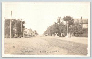 Miller SD~Men on Benches~Apartments?~Dirt Broadway~Sign Leans~RPPC c1916