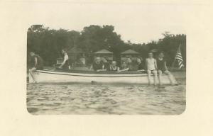 Men in Old Fashioned Swimsuits on Canoe, U S  Flag 1920s (?)  RPPC Postcard