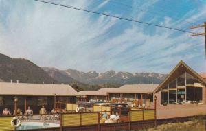 Patrons relax next to swimming pool at Lazy T Motel, overlooking Lake Estes, ...