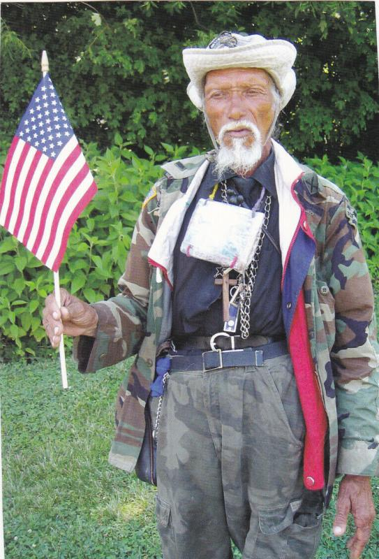 Native Man in Camo outfit holding American Flag, 1960-70s