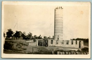RPPC~Trio of Men Sit Atop Water Tower~Construction of Stone Plant Below~c1916 PC