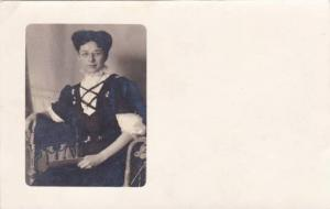 Lady wearing corset top  dress sitting in chair with letter in hand, 10-20s