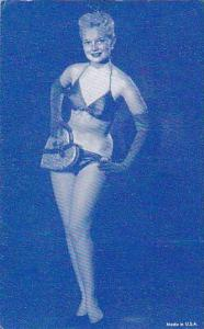 Blond Stripper in black satin bikini and gloves holding heart shaped chocolat...