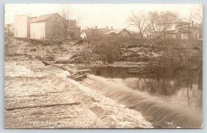 New Lisbon Wisconsin~Isn't this Dam Pretty? Not~Homes~Back of Store~1929 RPPC