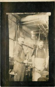 2 Blacksmiths in Shop~Hammer & Anvil~Pulley~Tools~Aprons~1912 Real Photo~RPPC