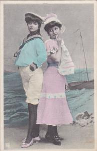 Woman dressed as a sailor another in a pink dress, by the ocean, sail boat in...