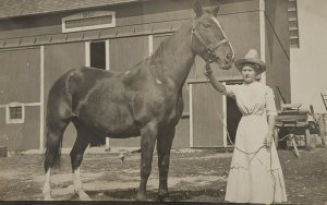 C.1904-1920. Woman In White Dress Handling Large Horse. Draft horse. Barn