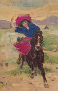 EMBOSSED, 1900-10s; Cowgirl on galloping horse twirling a lasso