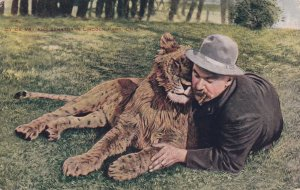 Man snuggling with young lion on the grass, PU-1908
