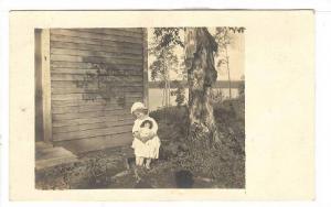 RP; Girl holding doll enjoying the sunshine siting on stool, 10-20s