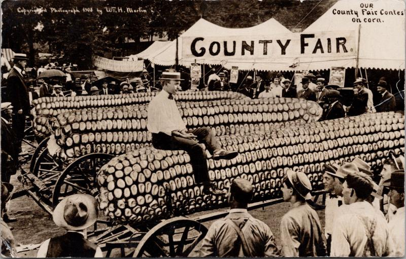 Man Sitting Corn Cob County Fair Exaggerated c1911 W. Martin RPPC Postcard E35