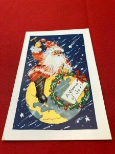 embossed postcard SANTA sitting on earth with hammer to nail a wreath on world