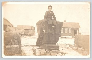 Real Photo Postcard~Boy Sits on Snow Sleigh Roof Top~Farm Barns~c1910 RPPC