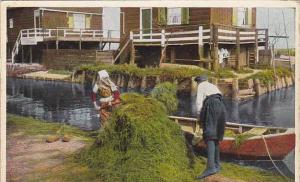 Couple plowing hay in row boat, Marken, North Holland, Netherlands, 10-20s
