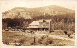 Libby Lodge~Parked Cars~Man on Steps~Note on Back~Meyers RPPC pm @ Rawlings WY