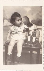 RP; Boy holding red ball sitting next to toy dog on a table, 10-20s