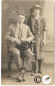 Vintage Postcard Real Photo RPPC of Man Sitting in Large Pallor Chair and Woman