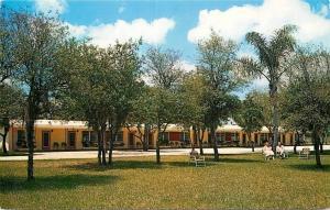 Avon Park FL~Southernaire Motel~1950s Postcard~Older Couple Lounges on Grounds