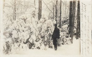 RP: Man standing by snow covered trees, holding container, PU-1907
